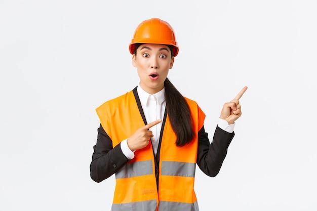 건축, 건설 및 산업 개념. 흥미로운 제품이나 물건에 대해 질문하는 감동적이고 놀란 아시아 여성 엔지니어. 건축가 가리키는 손가락 오른쪽 상단 모서리.