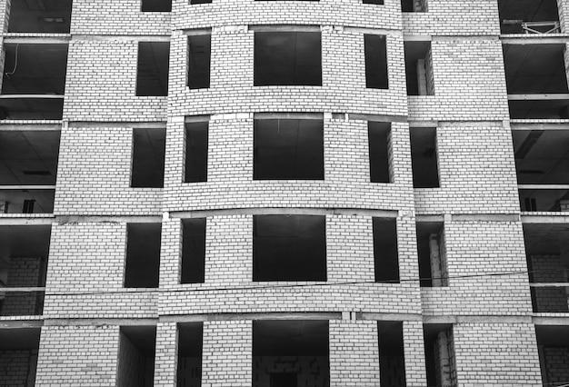 Building under construction, concrete walls and white bricks. facade background photo