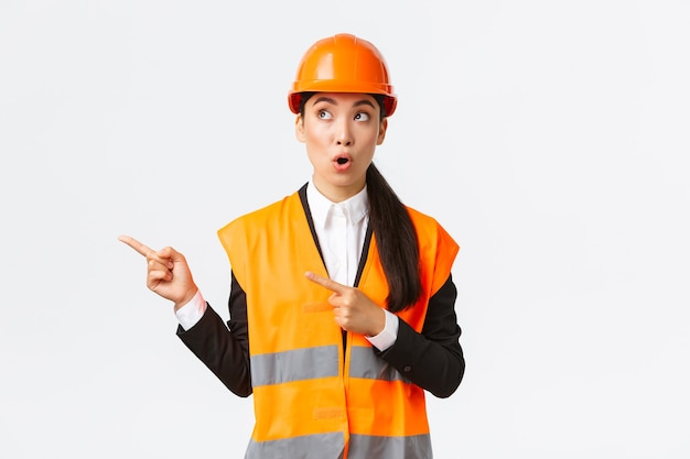 Building, construction and industrial concept. intrigued and surprised female engineer, asian architect in helmer and reflective clothing, pointing fingers upper left corner and saying wow