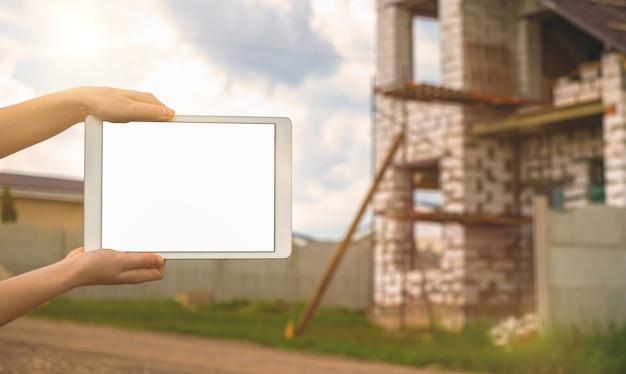 Макет строительства, планшет с черно-белым экраном в руке на фоне недостроенного дома, копия космического фото