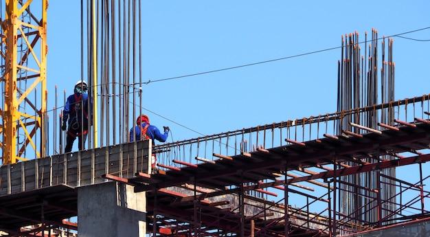 鉄骨とコンクリートの材料と青い空の上に立っている建物の建設現場と労働者。