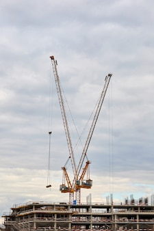 Building under construction and tower cranes against the sky