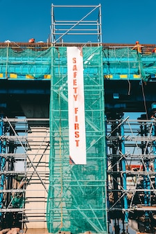 A building under construction with safety first banner