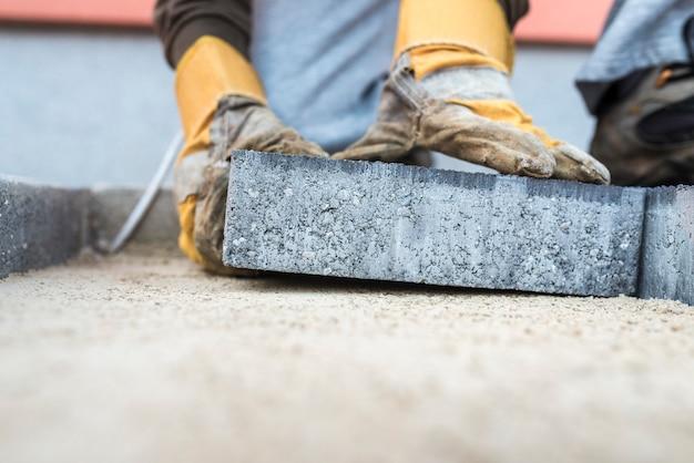 Строительный подрядчик укладывает тротуарную плитку