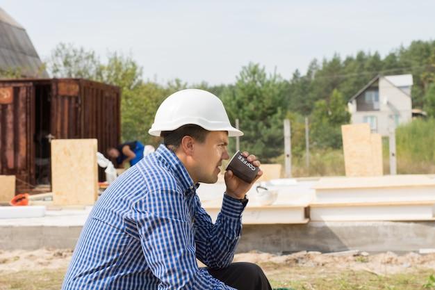 彼の後ろに新しい家の基礎とプロファイルに座って現場でコーヒーブレイクを取っている建築請負業者