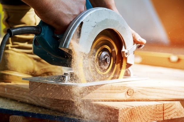 Building contractor worker using hand held worm drive circular saw to cut boards