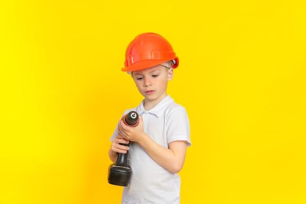Обучение строительному ремеслу. мальчик в каскуке стоит на желтой стене и внимательно смотрит на строительный электроинструмент. профессия строитель, развитие детей.