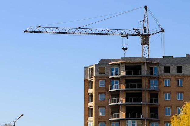 Строительный кран и строящееся здание против голубого неба
