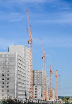 クレーンの建設と曇り空を背景に建設中の建物 Premium写真