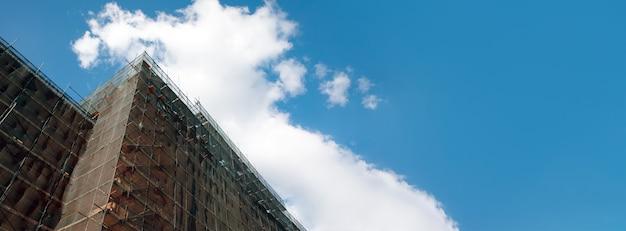 青空の建物のファサードの改修、古い家の再建、修理。透明な生地で覆われた建物のファサードの前の足場、パノラマレイアウト