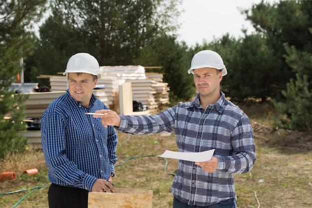 フレームの左側にペンで指している同僚と一緒にドキュメントを持って立って指示を与える建物の職長またはエンジニア