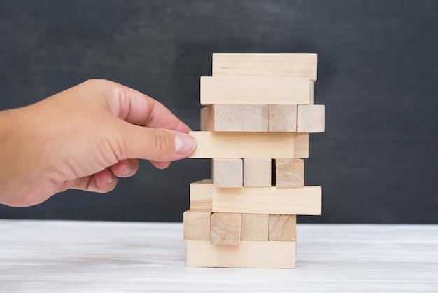 나무 블록으로 건물. 배경에 손으로 나무 블록 스택 게임. 팀워크의 개념입니다. 아키텍처 모델이 있는 블록 타워, 관리 및 전략 계획의 위험, 성장 비즈니스 성공