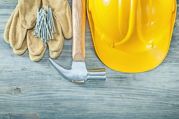 建物のヘルメット革保護手袋爪ハンマー木の板の建設コンセプトの爪