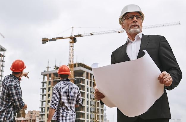 正装と白いヘルメットを保持している経験豊富な年配のエンジニアの建物の検査官の肖像画