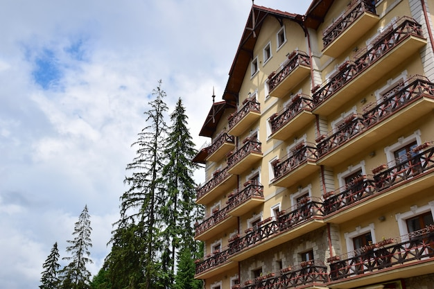 The building is a large multi-storey hotel with balconies against the backdrop of sky and trees there are no people in the photo, there is a place to insert text on the left