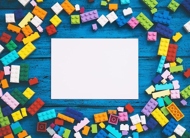 Строить детские пластиковые блоки на столе с пустым блокнотом для текста