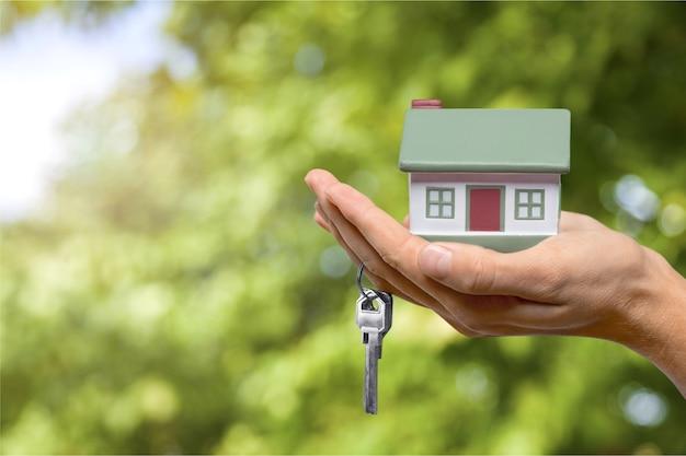 건물, 모기지, 부동산 및 부동산 개념 - 손을 잡고 집 모델을 닫습니다.