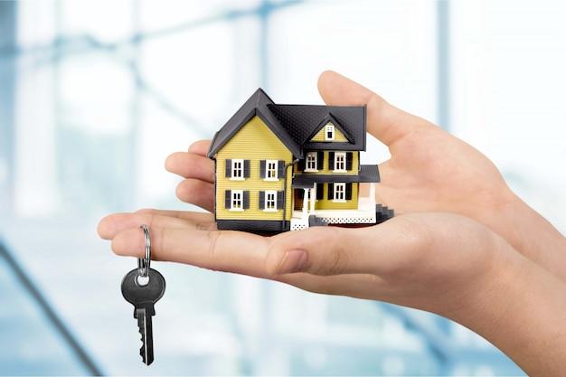 건물, 모기지, 부동산 및 부동산 개념 - 집 모델을 들고 있는 손 클로즈업