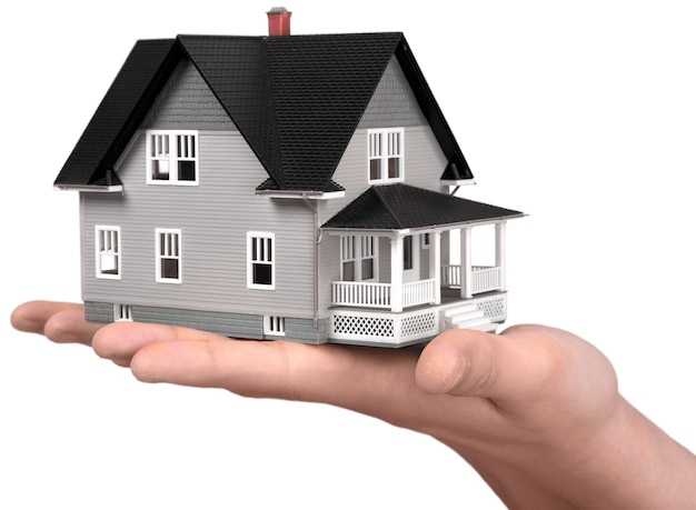 Building, mortgage, real estate and property concept - close up of hand holding house model