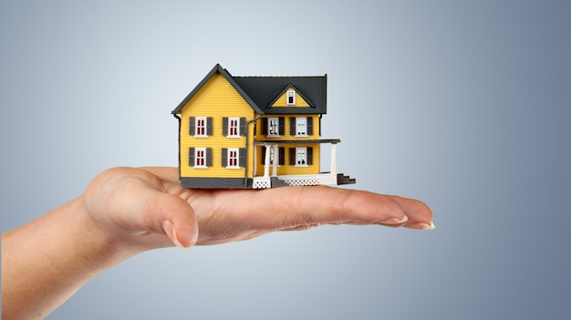 Building, mortgage, real estate and property concept - close up of hands holding house model