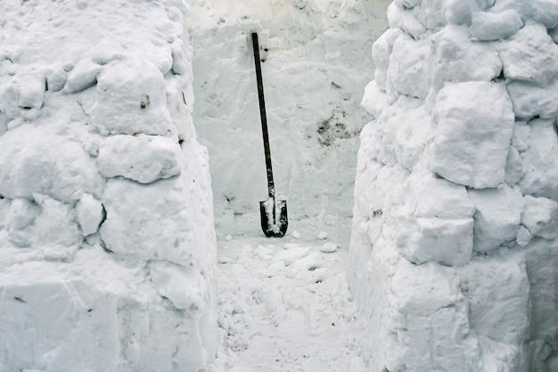 삽을 사용하여 눈 벽돌에서 추운 겨울에 눈 집 이글루 건설