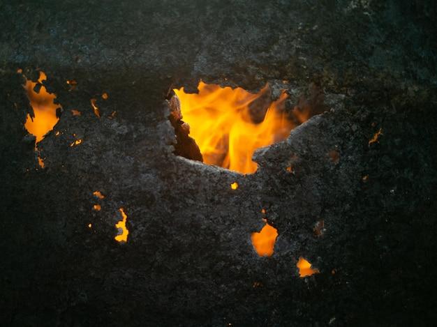 火の上に構築することは燃えるような火を閉じます焦げた穴の火の概念を通して明るい火