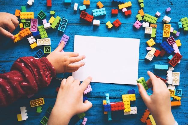 空白のカードまたはテキスト用の空のメモ帳でテーブルにプラスチックブロックを構築する