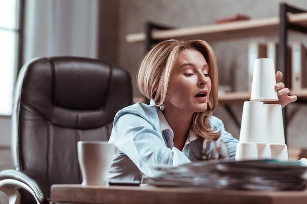 건물 피라미드. blonde-haired 여자는 안경에서 피라미드를 구축하는 직장에서 지루함을 느끼고