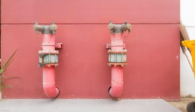 빨간 콘크리트 벽에 건물의 금속 배관 시스템