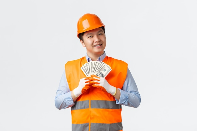 Концепция строительного сектора и промышленных рабочих довольна довольным азиатским строителем-строителем в ...