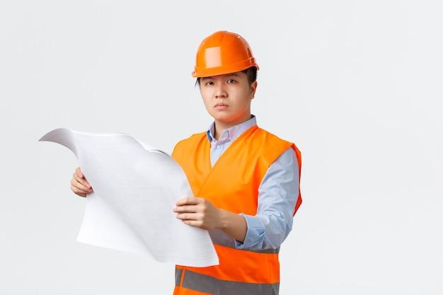 建築部門と産業労働者の概念。真面目な自信を持ってアジアの建設マネージャー、ヘルメットと反射ジャケットのエンジニアが青写真を見て、レイアウトをチェックし、白い背景。