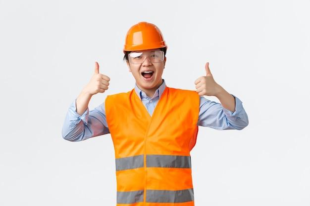 建築部門と産業労働者の概念。安全ヘルメットと親指を立てる反射服で笑顔のアジア人男性エンジニア、建築家またはビルダーは、すべてが大丈夫であることを保証します