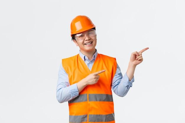 Settore edile e concetto di lavoratori industriali. il costruttore asiatico sorridente allegro, il responsabile della costruzione in casco e l'abbigliamento riflettente che indicano l'angolo in alto a destra, dimostrano, fondo bianco.