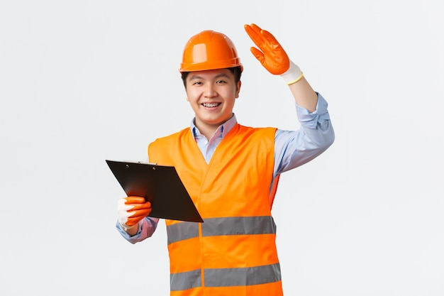 Settore edile e lavoratori industriali concetto allegro sorridente ispettore direttore di costruzione asiatico...