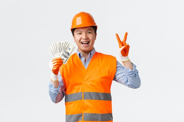 Building sector and industrial workers concept. happy smiling asian builder, construction manager in helmet and reflective clothing showing peace sign and money, got salary, white wall.