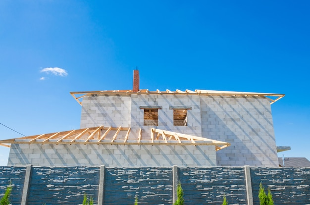 白い発泡コンクリートブロックで作られた建設中の家の建築現場。家の新しいフレームを構築します。