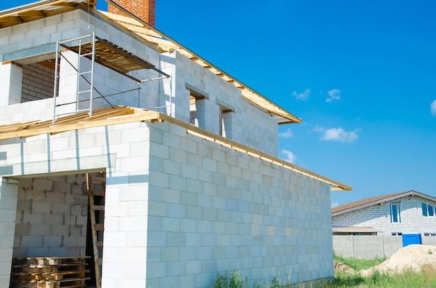白い発泡コンクリートブロックで作られた建設中の家の建設現場。家の新しいフレームを構築します。