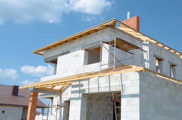 Строительная площадка строящегося дома из белых пеноблоков с новым каркасом