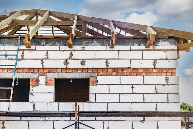 건설 중인 집의 건물 사이트입니다. 흰색 폭기된 오토클레이브 콘크리트 블록으로 만든 미완성 주택 벽. 나무 트러스 시스템.