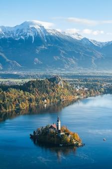 Edificio su una piccola isola a bled, in slovenia, circondato da alte montagne