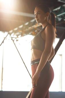 理想的なボディを構築します。スポーツ服を着てジムに立って、トレーニング後に休んでいる間、目をそらしている若い美しい運動女性の垂直ショット。スポーツ、トレーニング、健康的なライフスタイル