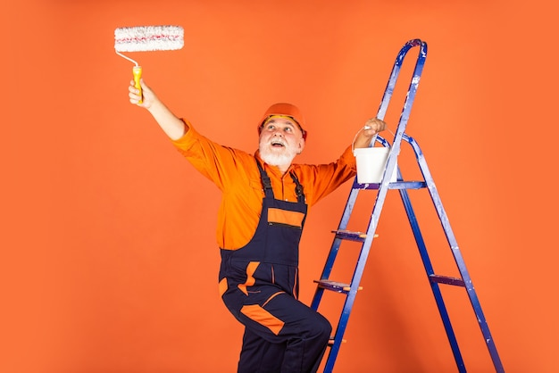 Оборудование для ремонта строительного инструмента. старший художник использует ролик на лестнице. покраска стены в оранжевый цвет. художник в рабочей одежде. стена картины рабочего в комнате. мужской декоратор роспись валиком.