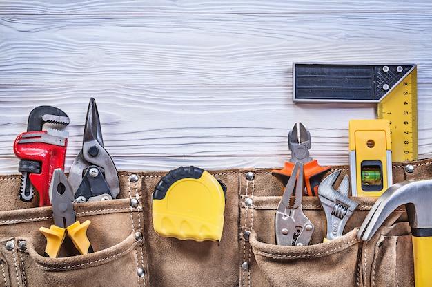 Строительные инструменты в кожаном поясе для инструментов на деревянной доске