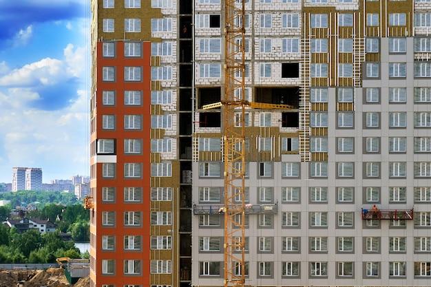 Строящееся здание с рабочими в строительных люльках в москве