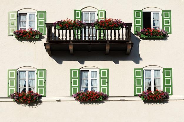 꽃으로 장식 된 녹색 셔터가있는 창문과 발코니가있는 건물 전망.
