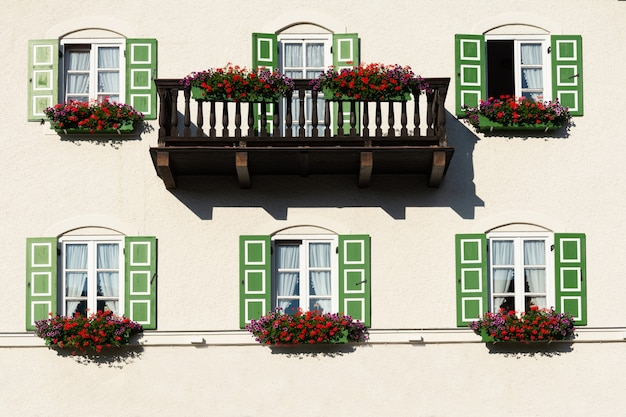 Building view with balcony and windows with green shutters decorated with flowers.
