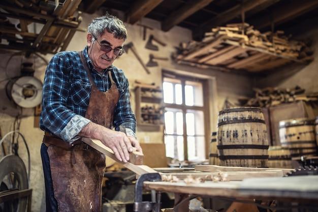 빈티지 작업장에서 노인이 숙성된 알코올을 저장하기 위한 나무 통을 만듭니다.