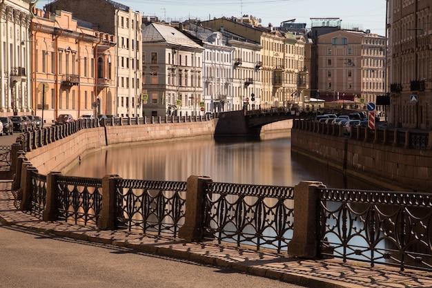 전경에 제방의 단철 울타리와 흐린 물에 반사 된 상트 페테르부르크의 역사적인 중심지에있는 작은 강을 따라 건물