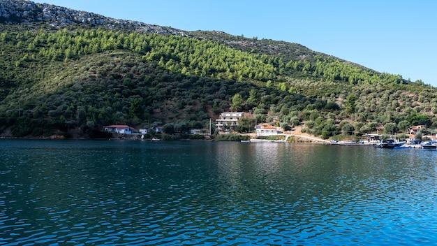 Постройки и пришвартованные лодки у воды, много зелени, зеленые холмы, греция