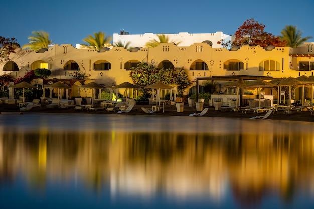 건물, 일광욕용 라운저, 파라솔은 이집트 샤름 엘 셰이크(sharm el sheikh) 리조트 타운의 밤에 해변의 잔잔한 바닷물에 반사됩니다.